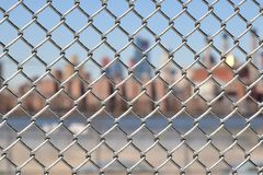 Urban Chain Link Closeup Abstract Texture Background. Chain link fence closeup abstract texture background with urban city skyline background Royalty Free Stock Images