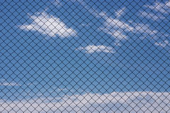 Chain link fence. Clouds grid metal sky Stock Images