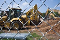 Chain Link Fence At Construction Site. Looking through a chain link fence at a construction site royalty free stock image