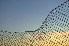 Chain link fence on evening sky Royalty Free Stock Photography