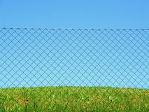 Chain link fence grass sky Royalty Free Stock Image