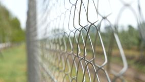 Chain-Link Fence. orchard fence. Chain-Link Fence background of an orchard. summer day stock video