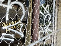 Abandoned shop, Austin, Texas. Chain link fence over abandoned storefront with graffiti over glass and business hours written in Spanish royalty free stock photo