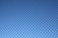 Chain link fence pattern. Chain link fence, a bit old and rusty, on a blue sky background stock images