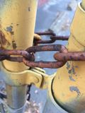 Chain link fence poles locked rusty rust grunge yellow peeling paint metal Stock Image