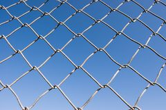 Chain Link Fence (series). Closeup of a chin link fence with blue sky in the background Royalty Free Stock Images