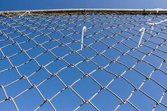 Chain Link Fence (series). Closeup of a chin link fence with blue sky in the background Stock Photos