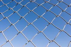 Chain Link Fence (series). Closeup of a chin link fence with blue sky in the background Royalty Free Stock Photography