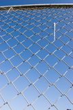 Chain Link Fence (series). Closeup of a chin link fence with blue sky in the background Royalty Free Stock Photos