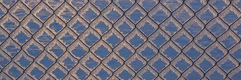 Chain-link fence with snow, winter background Stock Photo