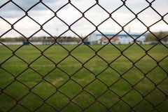 Chain link fence in a sports park with grassy field behind it. Background barrier cage grid mesh metal net security wire pattern steel wall chainlink design stock photo