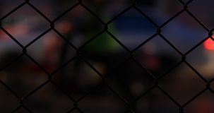 Chain-link fence on street. City night with traffic car driving on road, chain-link fence on street stock video footage