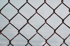 Chain-link fencing pattern. Chain-link old rusty fencing seamless pattern on grey background, metal wire mesh fence stock photo