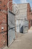 Warehouse outdoor security gate with circular barbed wire on red brick urban building. Chain link open door. Blue sky and wispy clouds. Vertical composition Stock Images