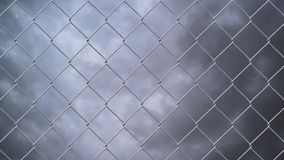Chain link wire fence against cloudy sky stock video footage