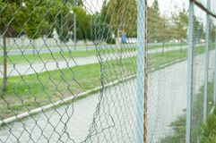 Chain link wire fence with hole in the line with street. Royalty Free Stock Photo