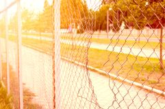 Chain link wire fence with hole parallel with the street and with sunlight. Stock Photography
