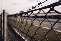 Chain-linked fence with barbed wire at top with grass and road in the background Stock Photo