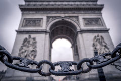Chain links and the Arc de Triomphe in the background. Metaphoric image with chain links sprinkled with rain drops in the foreground and the Arc de triumph on Royalty Free Stock Photo