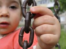 Chain links on swing in hands of small child Royalty Free Stock Photo