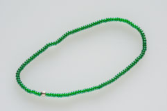 Chain with little green beads. String/ chaplet of green glass beads with one silver pearl, on white background Stock Photography