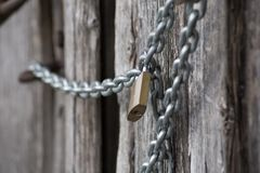 Chain lock on wooden wall. Very strong chain offer safe look together with lock on it Stock Image