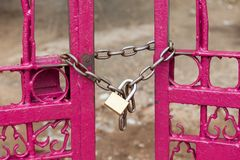 Chain locked on fence gate. Close up chain locked on pink color fence gate Stock Photo