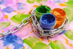 Chain metal and cans with paint for children`s creativity, colorful background painted with paint. Chain metal and cans with paint for children`s creativity Royalty Free Stock Image
