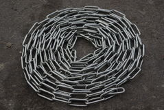 Chain metal. Folded metal chain lying on the dirty pavement Stock Image
