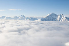 Chain of mountains sticking out of clouds Royalty Free Stock Photos