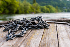 Chain over the planks of a river boat. A close up of a chain on the planks of a boat navigating on the still water of Rhine river with trees on background Stock Photos