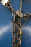 Chain and padlock. Blue wooden door secured by a thick metal chain and padlock Royalty Free Stock Photography