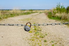 With chain and padlock closed rural country road. With chain and padlock closed gravelly rural country road royalty free stock photos