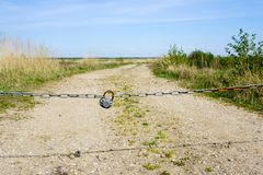 With chain and padlock closed rural country road. With chain and padlock closed gravelly rural country road stock photos