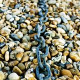 Chain on pebbles Royalty Free Stock Photos