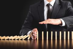 Chain Reaction In Business Concept. Businessman Intervening Dominos Continuous Toppling and Protecting Assets stock images