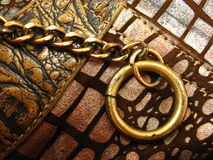 Chain-Ring Background. A background on a metal chain attached to a ring on a designer patchy surface Stock Photos