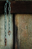 Chain rust. Rusty old chain that was hanging on the old wood walls Stock Photo