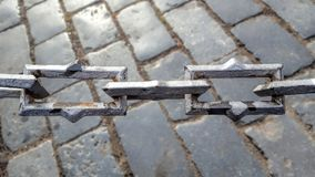 Chain sammanlänkningar över kullerstenstensida går Arkivfoton