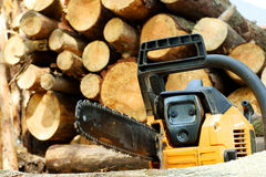 Chain saw. Against firewood pile royalty free stock photos