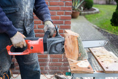 Chain saw cutting wood Stock Photos