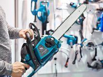 Chain saw in hands at store Stock Photos