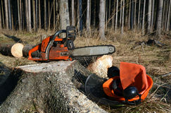 Chain saw, helmet on tree stump Stock Photography