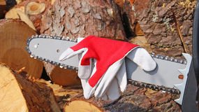 Chain saw - protective gloves. Chain saw and protective gloves. Wood background Royalty Free Stock Image