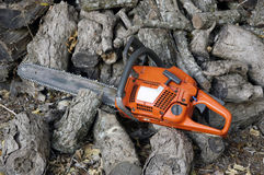 Chain Saw and Wood. A days work to be warm in winter Royalty Free Stock Photo