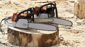 Chain saws. Chain saws for working with wood on a freshly felled tree stump Royalty Free Stock Photography