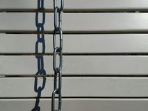 Chain. Silver chain seen against a background of light gray panels with spacing and with strong shadow Stock Photography