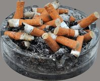 Chain smoking. Overflowing ashtray full of cigarette butts, disgusting showing filthy habit of chain smoking Stock Images