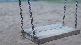 Chain swing moves. Chain swing without children and child swinging empty in cloudy weather