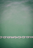Chain symbol of strong link and relationship. Metal chain across the frame green water in background Royalty Free Stock Image